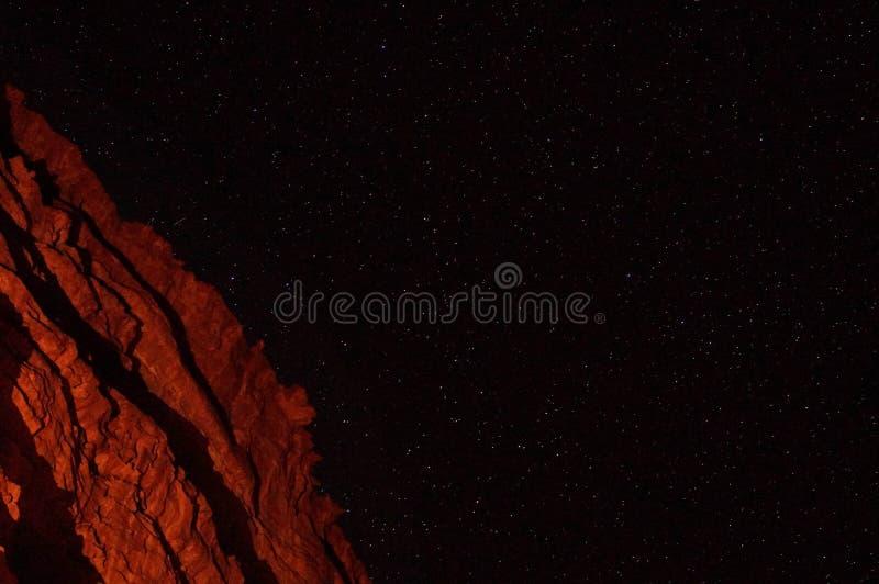 红色山在沙漠在与明亮的星的晚上 免版税库存图片