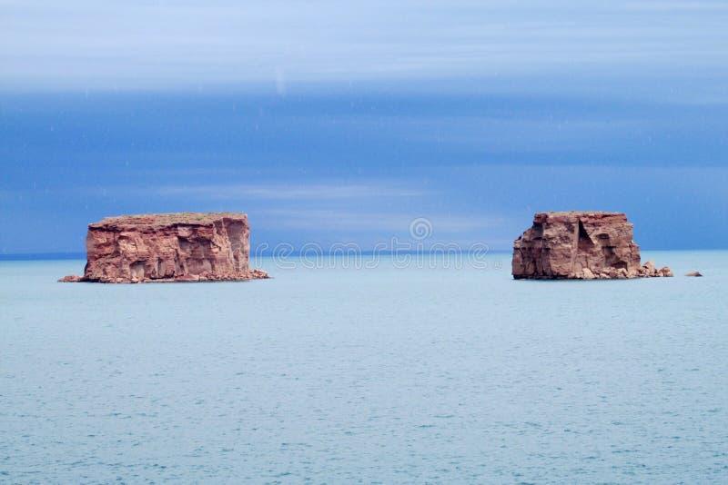 红色岩层在蓝色湖浇灌 图库摄影