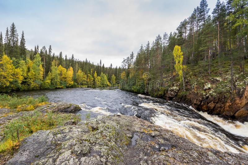 红色峭壁、石墙、森林、瀑布和狂放的河视图在秋天 图库摄影