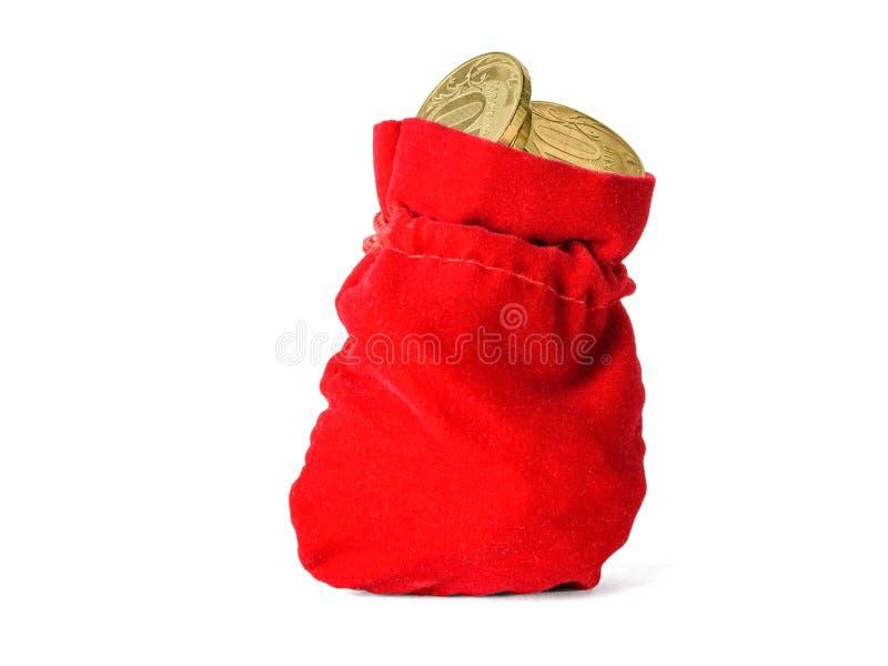 红色布料囊充满在白色背景隔绝的硬币 图库摄影