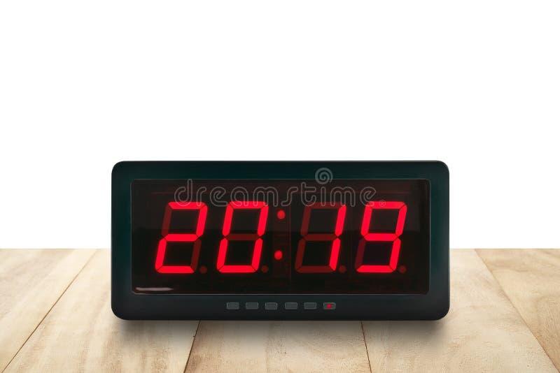 红色带领了轻的照明第2019年在棕色木桌上的黑数字电闹钟面孔 库存图片