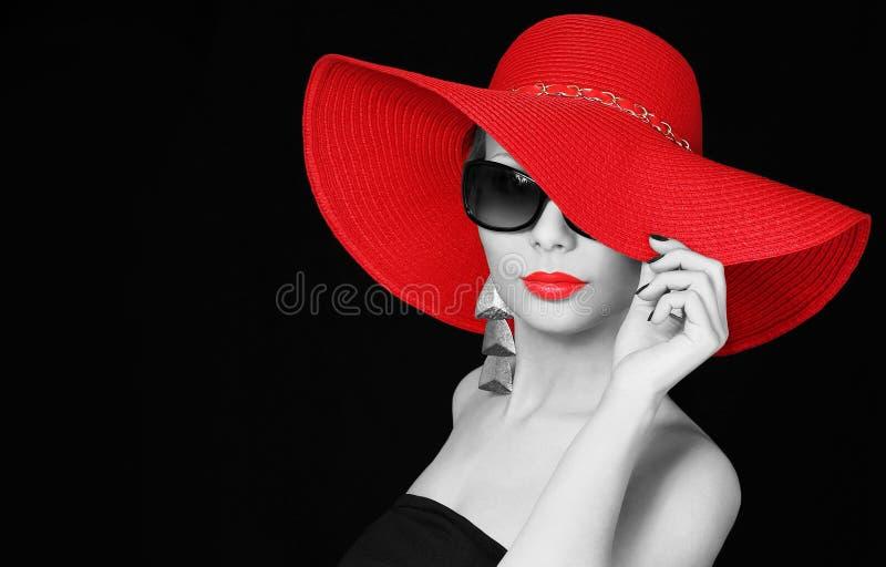 红色帽子和太阳镜的妇女在黑色 免版税库存照片