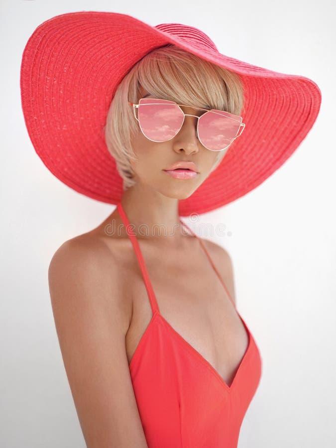 红色帽子和太阳镜的美丽的夫人 免版税库存图片