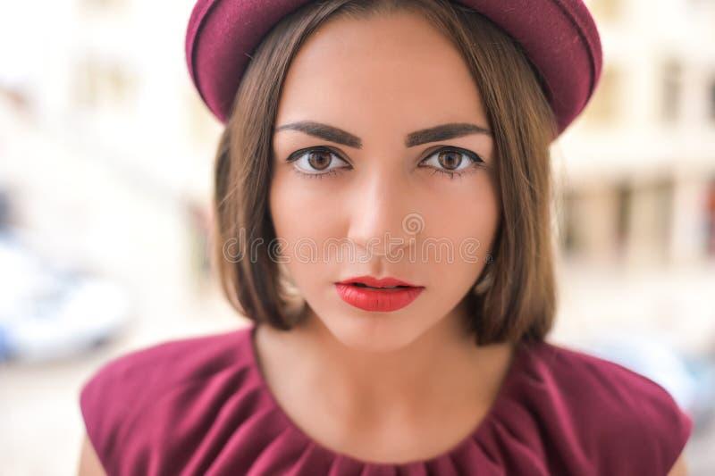红色帽子和礼服的美丽的夫人以催眠状态 图库摄影