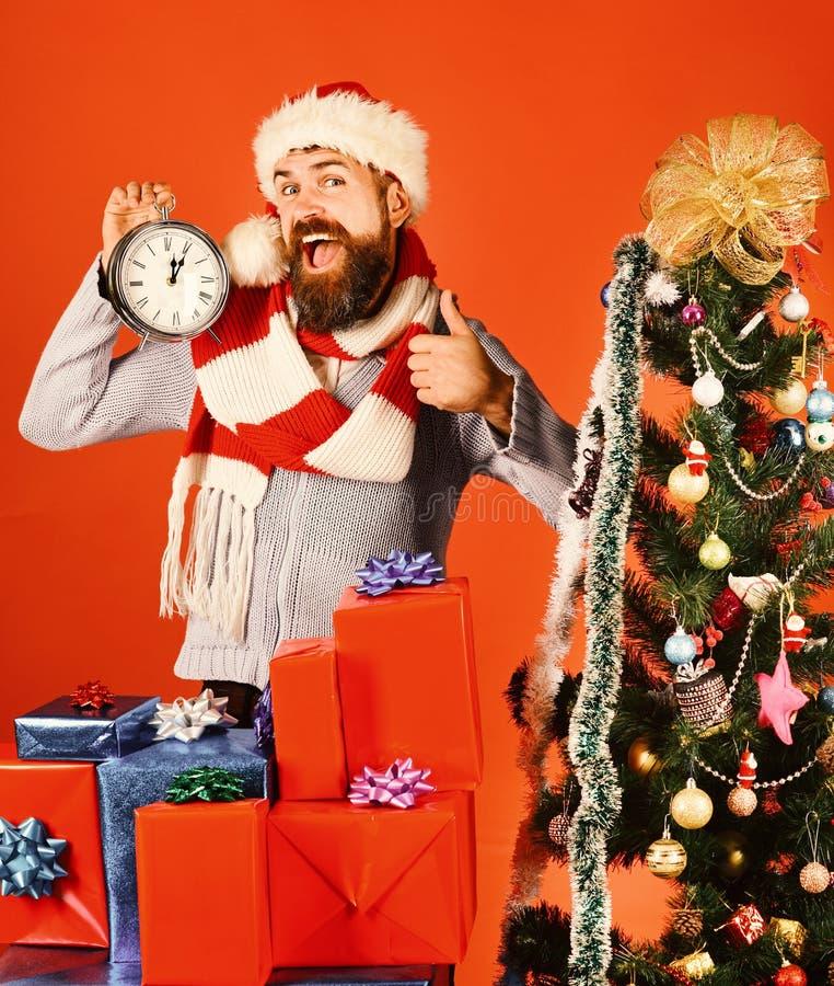 红色帽子的人有xmas礼物盒和时钟的 免版税库存照片