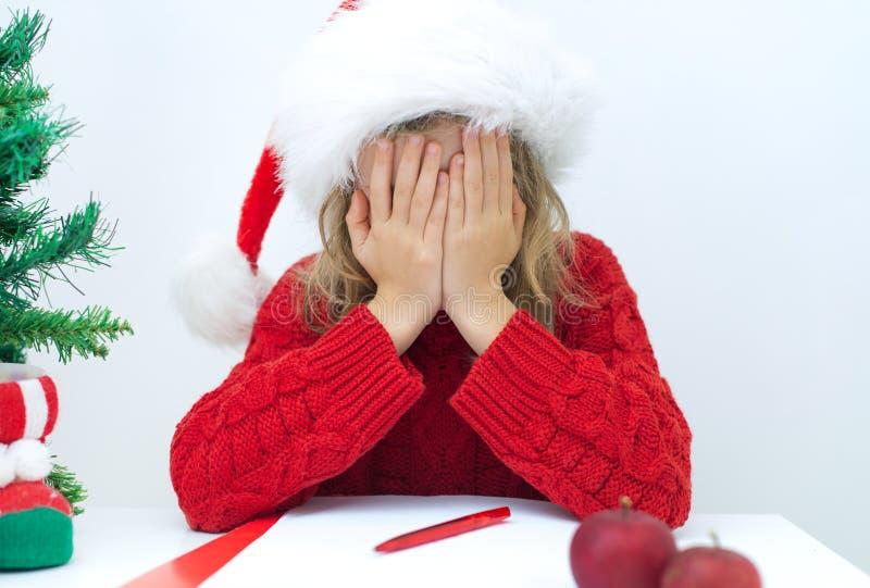 红色帽子的哀伤的小女孩 免版税图库摄影