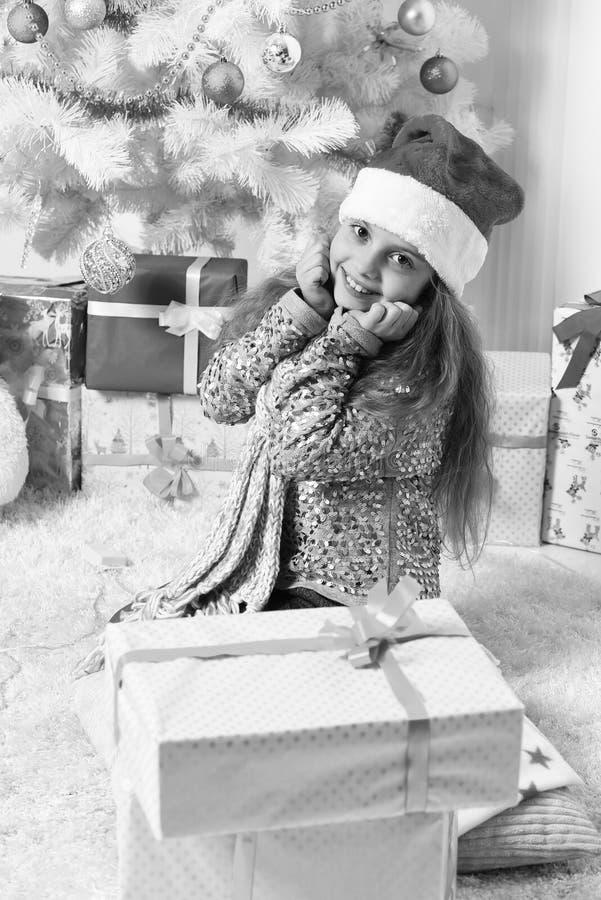 红色帽子的圣诞老人小姐在白色圣诞节树附近坐 图库摄影