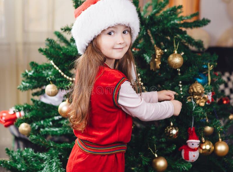红色帽子的小女孩装饰一棵圣诞树 库存图片