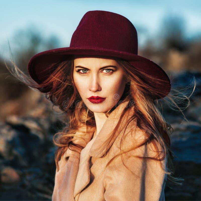 戴红色帽子的美丽的时髦的女人 库存图片