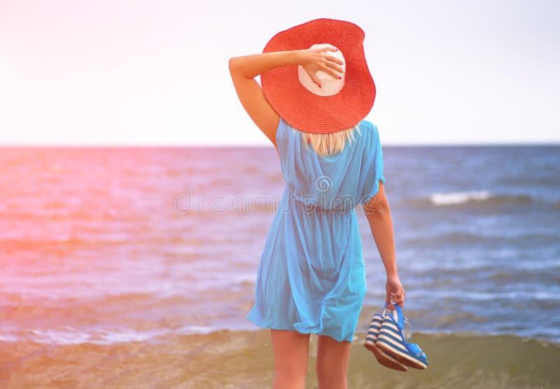 红色帽子的年轻俏丽的妇女在蓝色海附近放松 库存图片