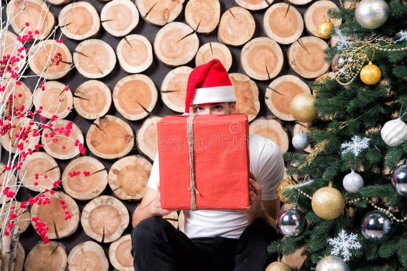 红色帽子窥视的圣诞老人人在当前箱子 免版税库存图片
