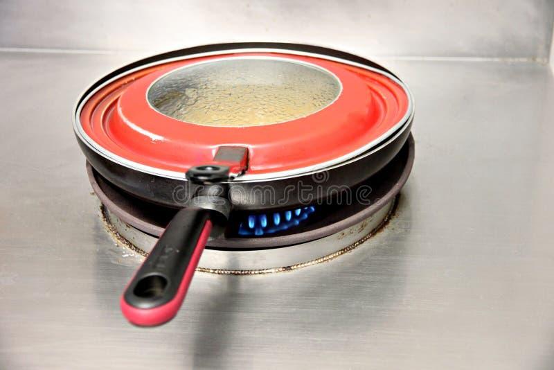 红色平底锅在火炉烹调。 库存照片