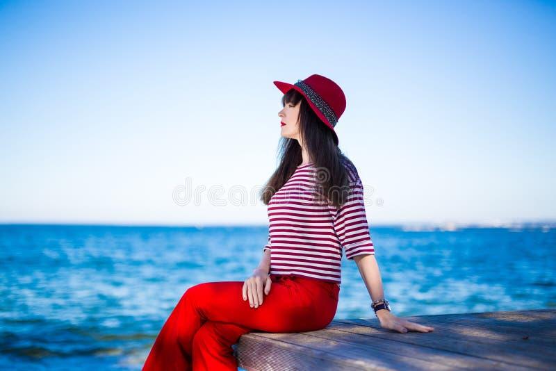 红色开会的可爱的妇女在蓝色海和天空 免版税图库摄影