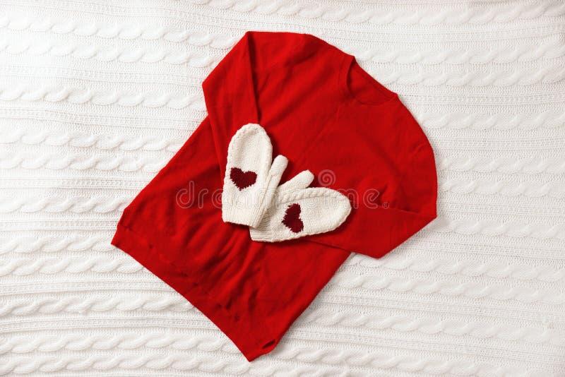 红色开士米毛线衣和手套在被编织的格子花呢披肩 库存照片