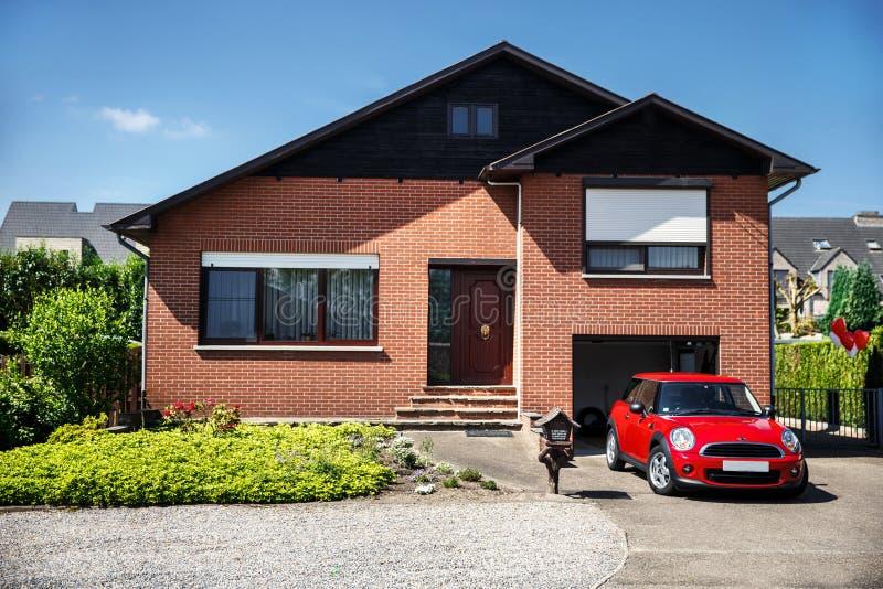 红色微型木桶匠和一个美丽的房子 免版税库存图片