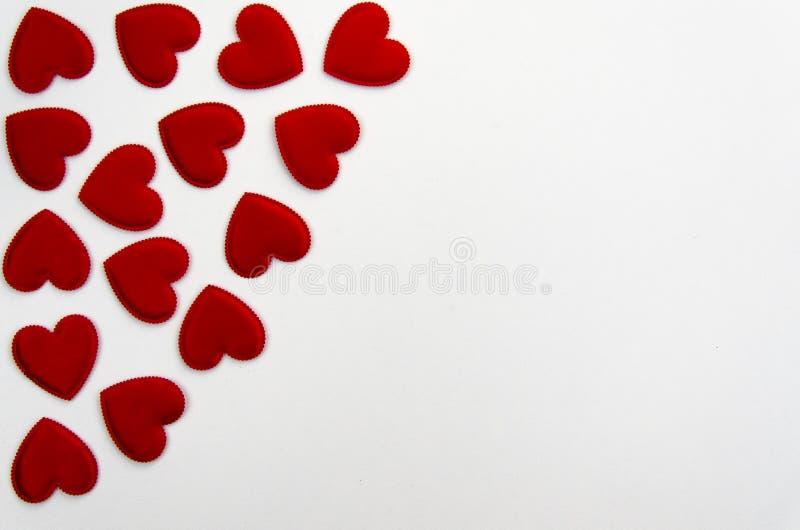 红色心形的五彩纸屑背景或角落边界在白色 顶视图,平的位置 免版税库存图片