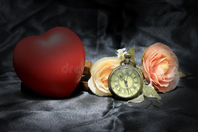 红色心脏和上升了与在黑织品背景的葡萄酒金怀表 时间概念爱  静物画样式 库存照片