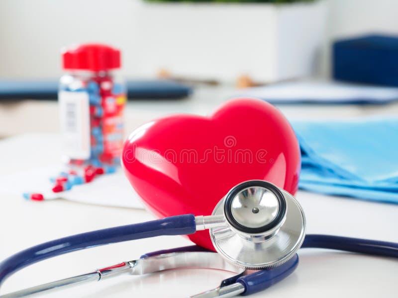 红色心脏和听诊器在医生桌上 免版税库存图片