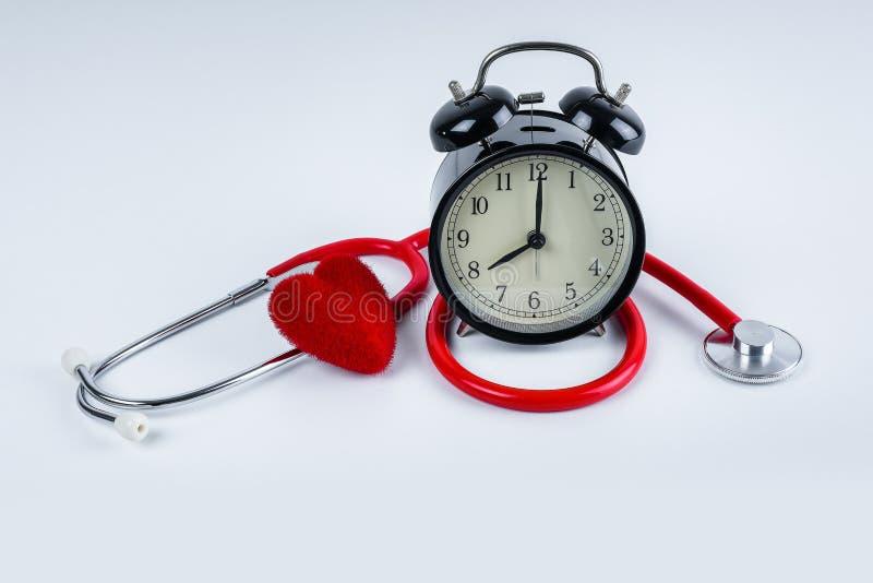 红色心脏和听诊器,在桌上的闹钟 免版税库存图片