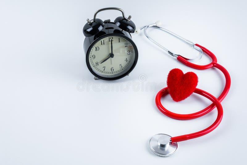 红色心脏和听诊器,在桌上的闹钟 免版税库存照片