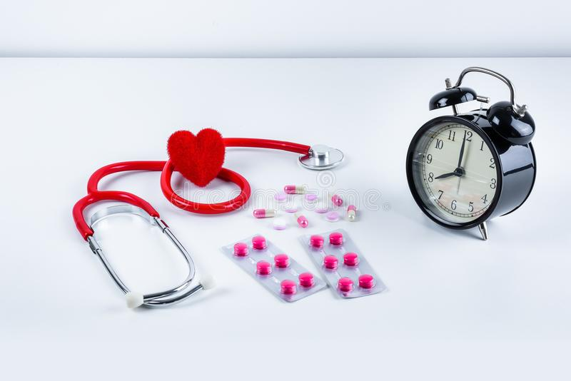 红色心脏和听诊器,闹钟,药物,在桌上的药片 图库摄影