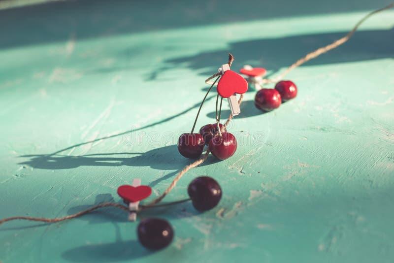 红色心脏和新鲜的红色甜樱桃在鲜绿色背景 概念卡片 安置文本 复制空间 爱和健康 免版税库存图片
