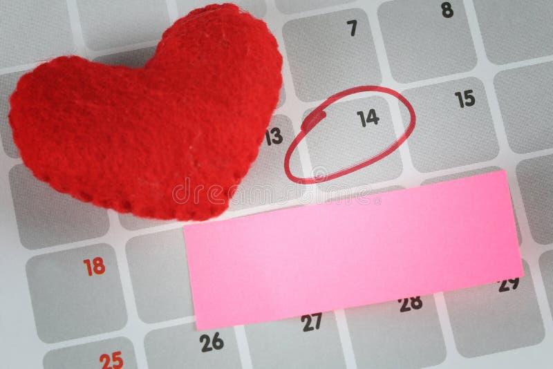 红色心脏和桃红色纸笔记在日历被安置 免版税图库摄影