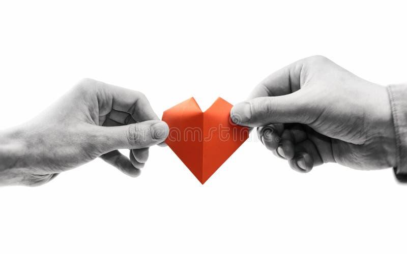 红色心脏在妇女和人手上 免版税库存图片
