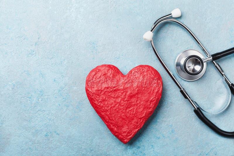红色心脏形状和医疗听诊器在蓝色背景顶视图 医疗保健、医疗保障和心脏病学概念 免版税库存照片