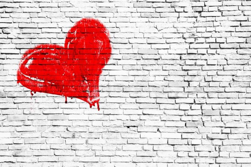 红色心脏手动地被绘在简单的脏的白色砖墙纹理背景 库存图片