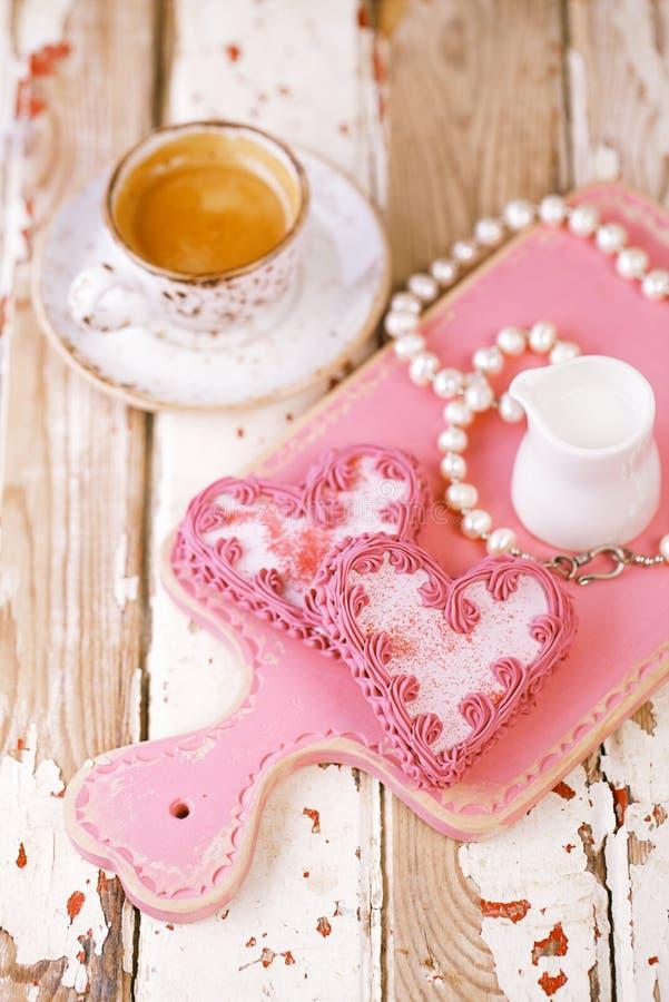 红色心脏曲奇饼和浓咖啡咖啡杯在老木桌上 库存图片