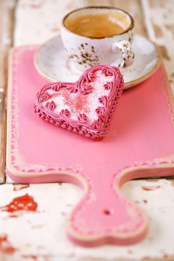 红色心脏曲奇饼和浓咖啡咖啡杯在老木桌上 免版税库存照片