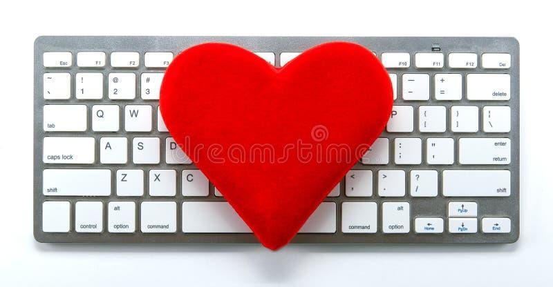 红色心脏的标志在键盘的作为约会标志 库存图片