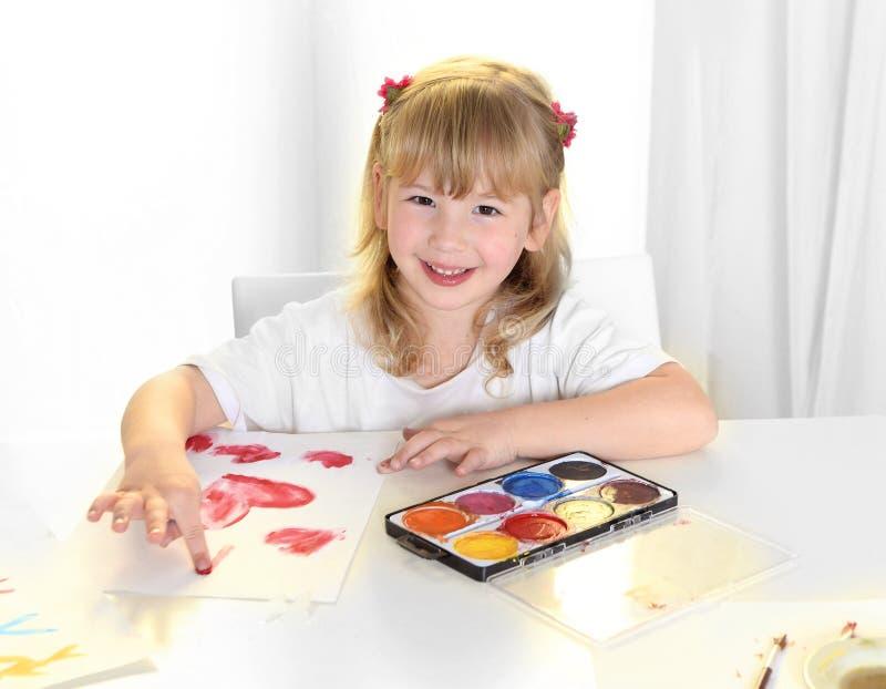 绘红色心脏的甜矮小的白肤金发的女孩 免版税库存照片