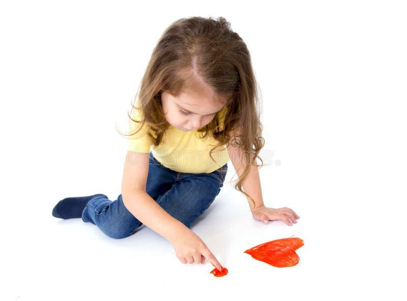 绘红色心脏的艺术性的甜小女孩 免版税图库摄影