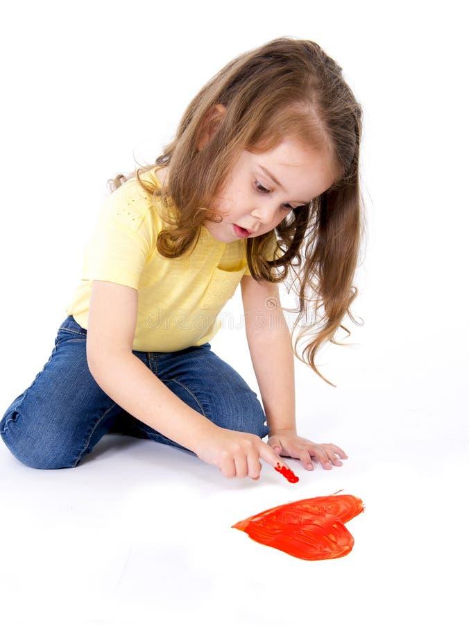 绘红色心脏的艺术性的甜小女孩 免版税库存照片