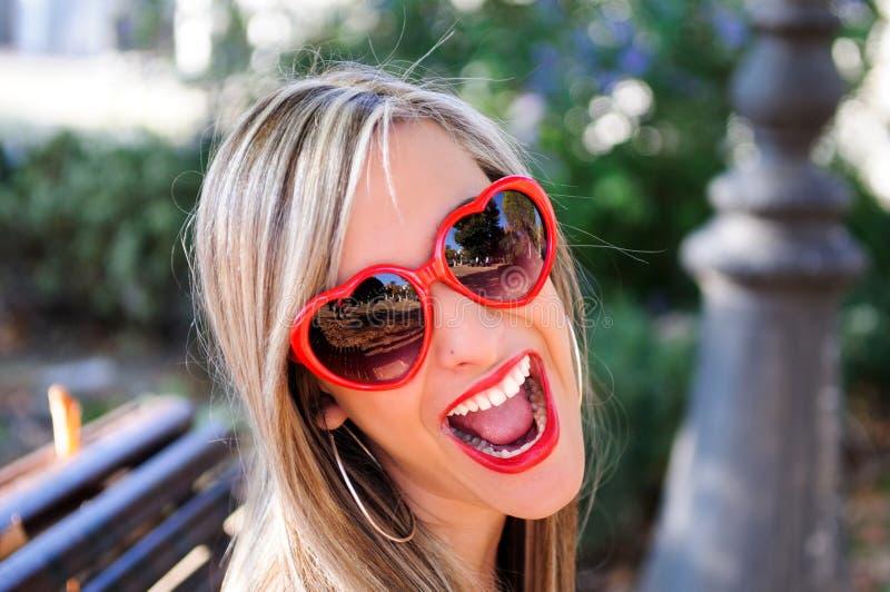 戴红色心脏眼镜的滑稽的女孩 免版税库存照片