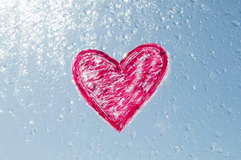 红色心脏绘与在窗口的唇膏用水下降 背景蓝色晴朗的天空,下落发光在阳光下 免版税库存照片
