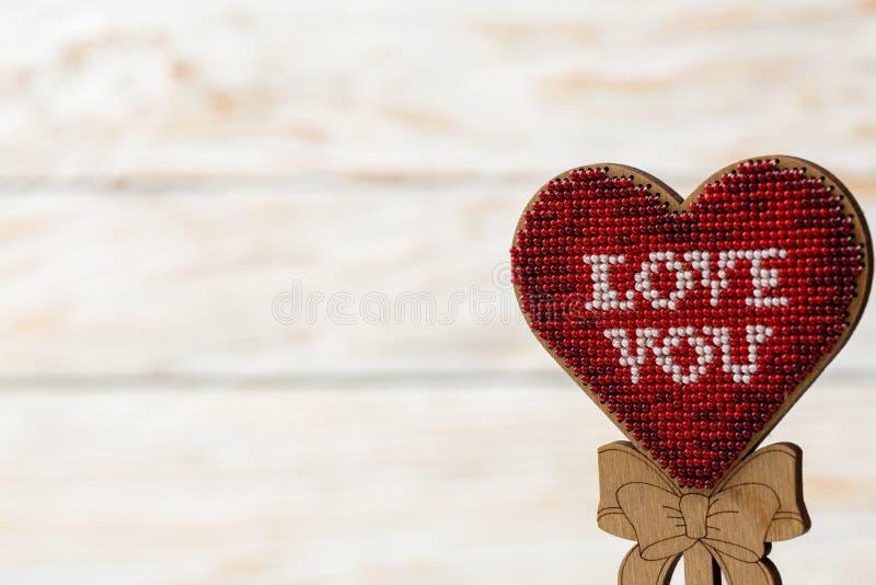红色心脏被绣在木白色背景的小珠 华伦泰` s天的概念 库存照片
