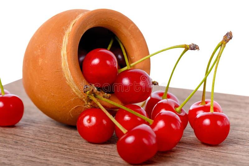 红色成熟樱桃莓果从罐驱散了到桌,被隔绝  免版税库存图片