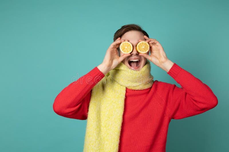 红色拿着柑桔的halfs毛线衣和黄色围巾的英俊的年轻人在手上,包括她的眼睛 免版税库存照片