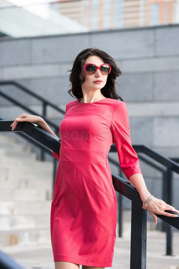 红色摆在台阶附近的礼服和太阳镜的引诱的夫人 免版税库存照片