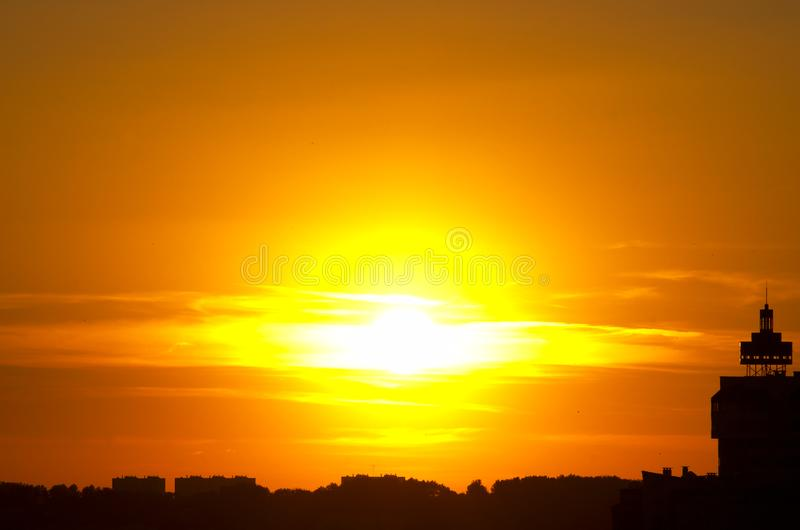 红色日落太阳疾风,在云彩的太阳,城市剪影 免版税库存图片