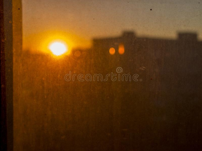红色日落看法在非常多灰尘和肮脏的玻璃后的 图库摄影