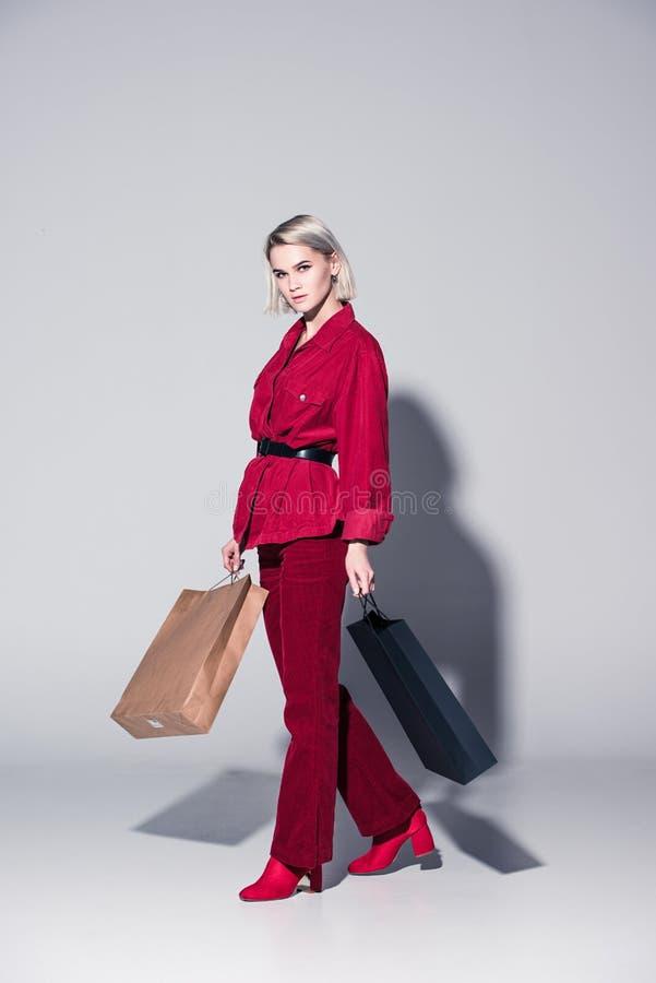 红色时髦衣裳的可爱的时兴的女孩有购物袋的, 免版税库存图片