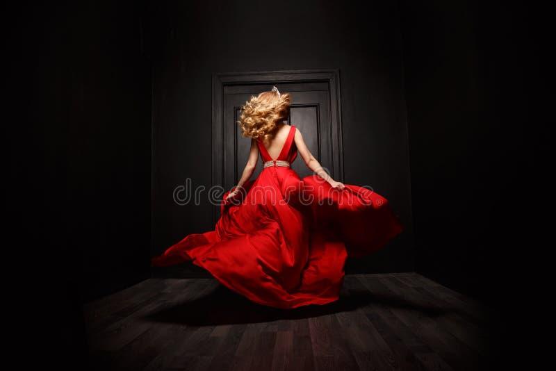 红色晚上振翼的礼服的典雅和性感的妇女是在移动的捕获,跑远离仪式 免版税库存图片