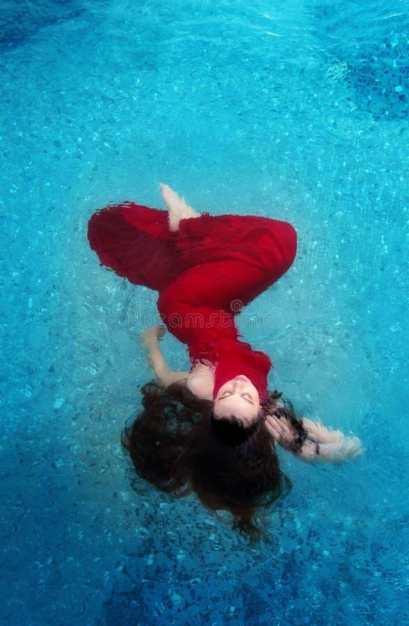 红色晚礼服典雅漂浮的美丽的年轻女人失重在水池黑褐色卷发浮动的水中 库存图片
