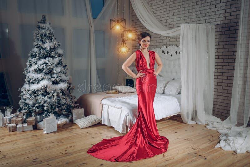 红色晚礼服的典雅的夫人在圣诞树背景 在别致或豪华内部 女孩去党 免版税库存照片