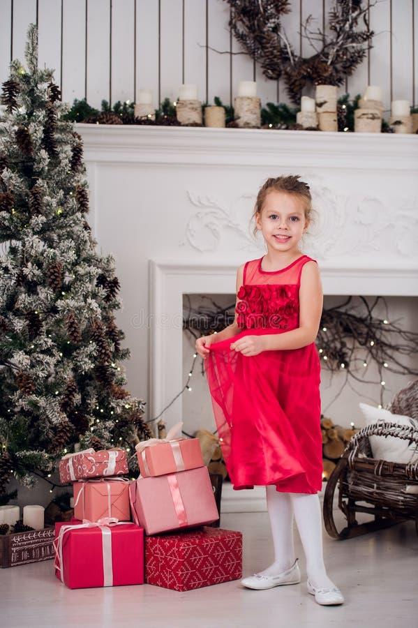 红色晚礼服的小美丽的女孩圣诞树 免版税库存照片