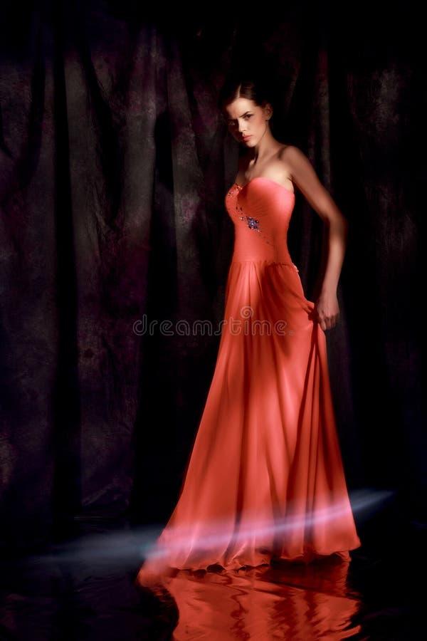 红色晚礼服的美丽的妇女在黑暗的背景 库存图片
